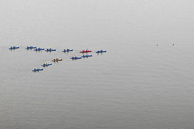 Kayaks paddle in a geese-like V-formation during Patrick Scully's boat ballet on the Havel River at Potsdam, Germany in 2010. (Photo courtesy of Patrick Scully, cribbed from StarTribune.com)