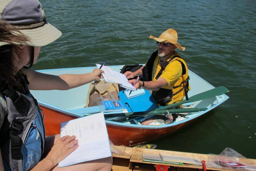 """Poet-in-residence Steve Healey and Floating Library founder Sarah Peters witness and dunk the 6 editions of """"A Book Dipped in Two Lakes."""""""